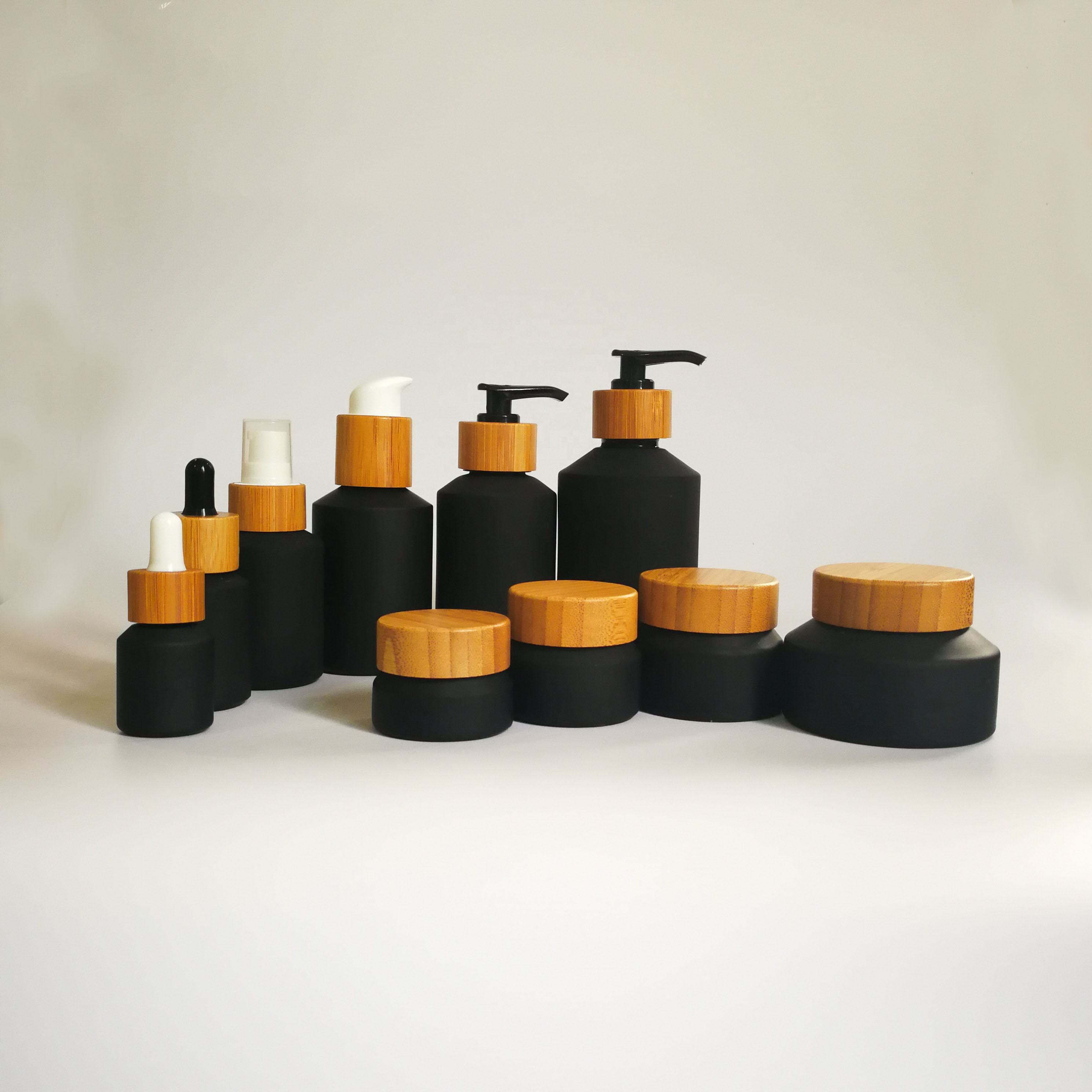Cosmetic packaging slant shoulder matte black skin care set black glass bottle with bamboo dropper and bamboo cap jar