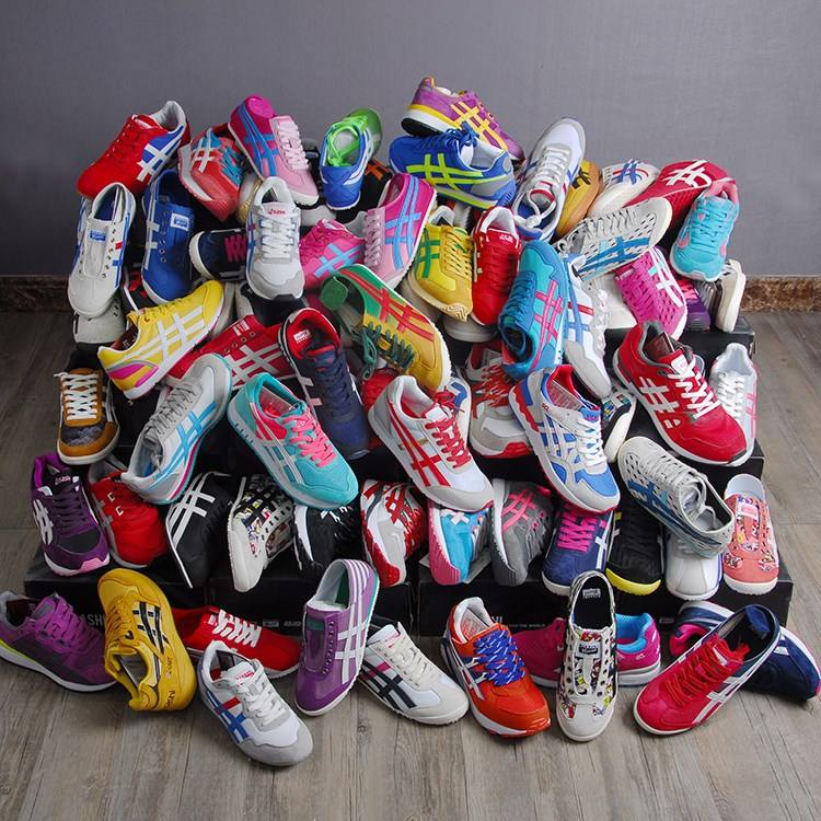A lot of mix used soccer shoes container of used clothes