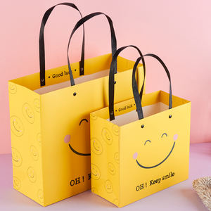 Hot sale happy face yellow art paper cartoon kraft christmas gift paper bag with plastic handle