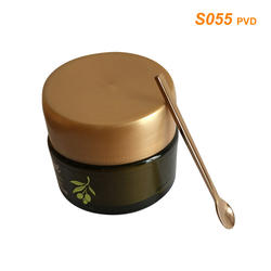 S055 PVD gold cosmetic spatula along with skincare cream jars